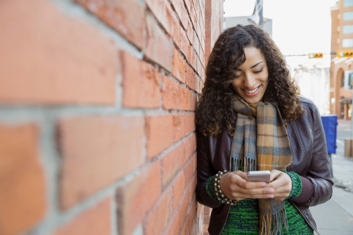 Young woman leaning against brick will, texting and laughing.