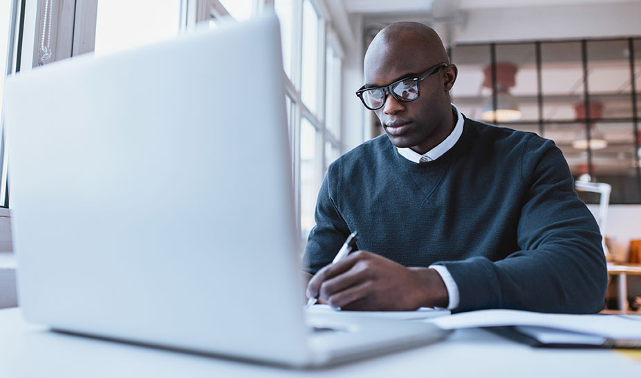 African American male , taking notes in front of laptop