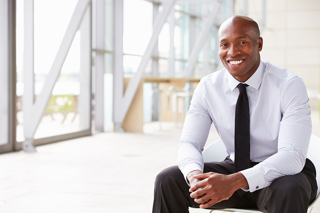 African American business man in chair smiling.