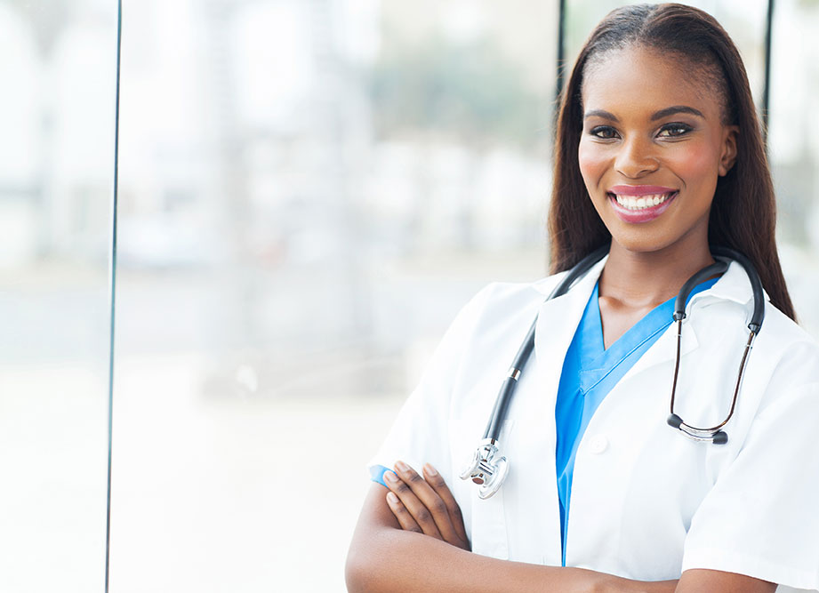Female African American doctor smiling, standing with your arms crossed.